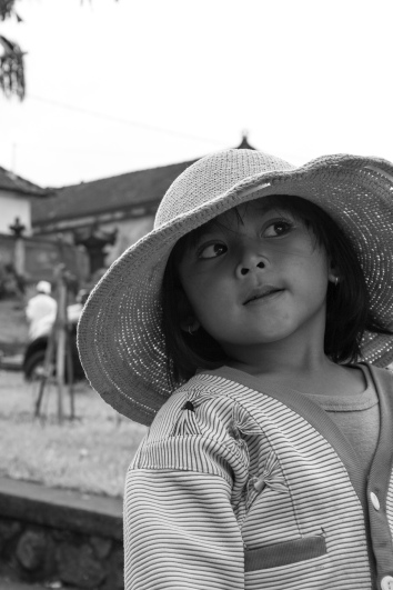 A little girl helping her mother sell flowers and offerings outside Pura Besakih.